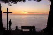 Thumbnail image of man viewing the sunset view of the coast by a cross from Riomaggiore, Cinque Terre, Liguria, Italy